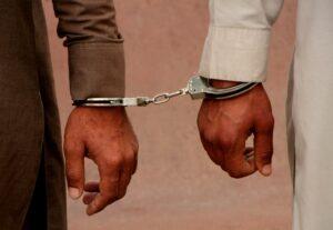 Drug smugglers stand handcuffed